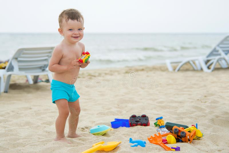 Младенец играя на песчаном пляже около моря стоковые фото
