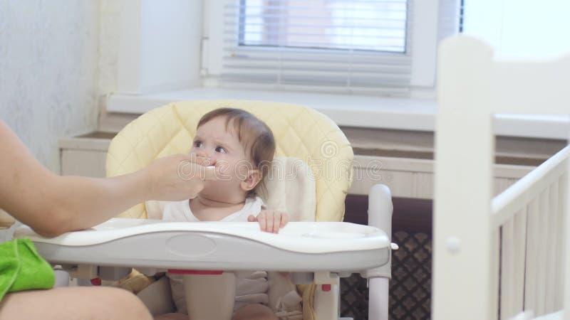 Младенец капризный и плача сидеть на высоком стульчике в кухне стоковые изображения