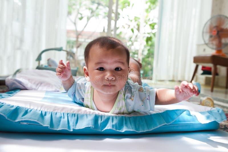 Младенец лежал на кровати в домашней живущей комнате стоковая фотография rf