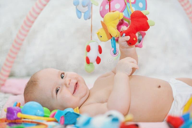 Младенец лежа на превращаясь половике играть в черни воспитательные игрушки Сладостный ребенок вползая и играя с игрушками на ков стоковое фото rf