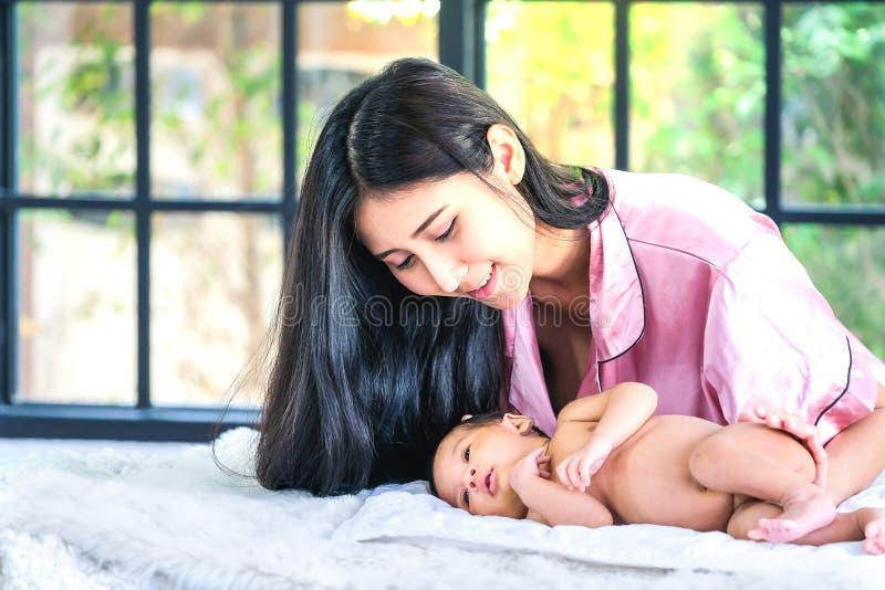 Младенец малыша в предложении обнимает матери на окне стоковая фотография rf