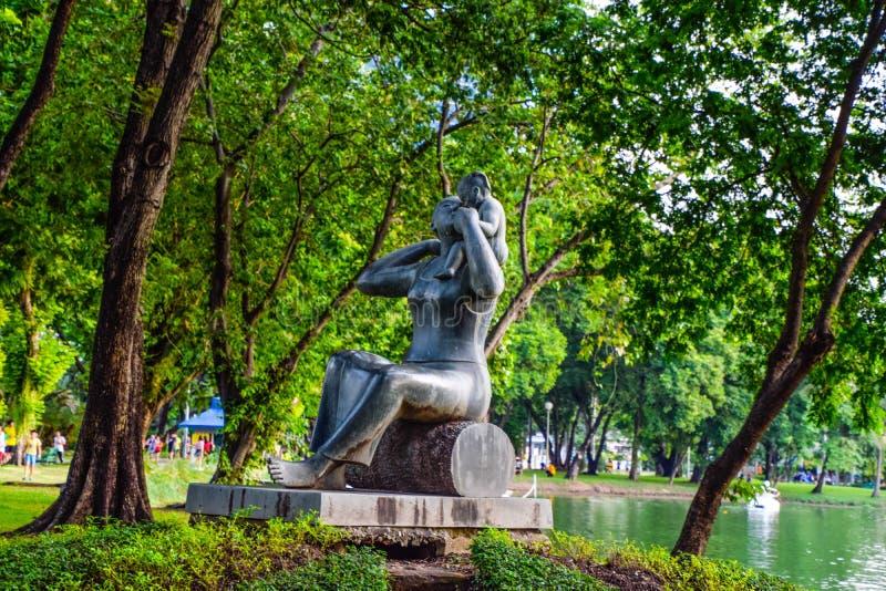Младенец нося статуи камня матери в парке на Бангкоке, Таиланде стоковая фотография rf