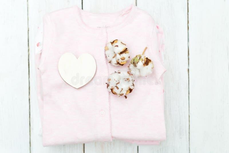 Младенец одевает от органического хлопка на деревянной предпосылке верхняя часть соперничает стоковые изображения rf