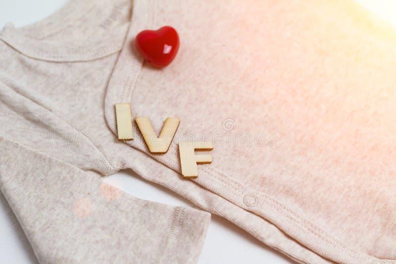 Младенец одевает с деревянным текстом IVF и сердцем Концепция - IVF, in vitro землеудобрение Ждать младенец, тонизированная берем стоковые изображения rf