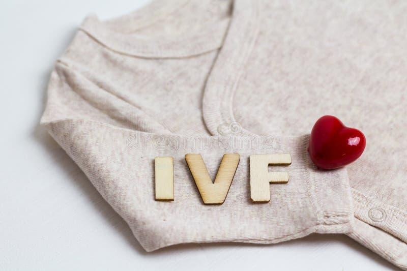 Младенец одевает с деревянным текстом IVF и сердцем Концепция - IVF, in vitro землеудобрение Ждать младенец, беременная стоковое изображение rf
