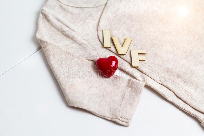 Младенец одевает с деревянным текстом IVF и сердцем Концепция - IVF, in vitro землеудобрение Ждать младенец, беременная стоковая фотография