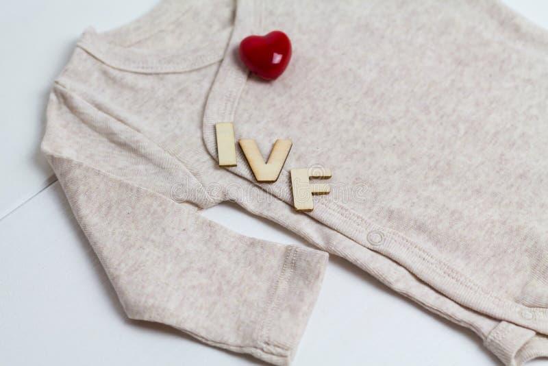 Младенец одевает с деревянным текстом IVF и сердцем Концепция - IVF, in vitro землеудобрение Ждать младенец, беременная стоковые фото