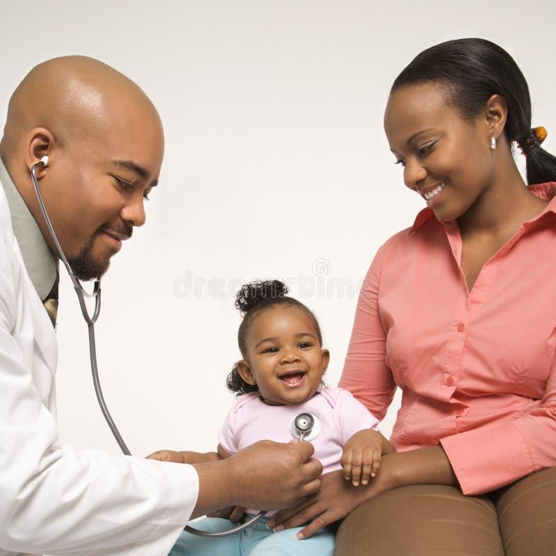 младенец рассматривает педиатр мати удерживания к стоковое фото rf