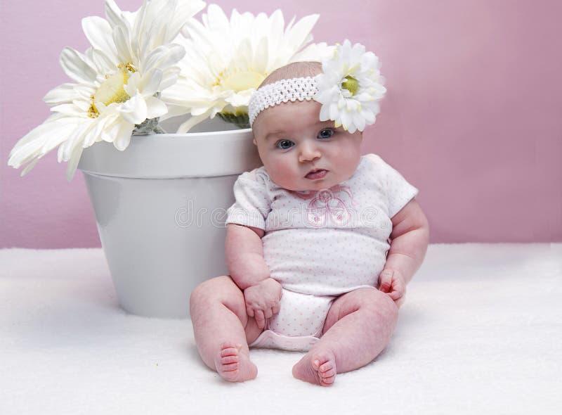 Младенец сидя рядом с цветочным горшком стоковое изображение rf