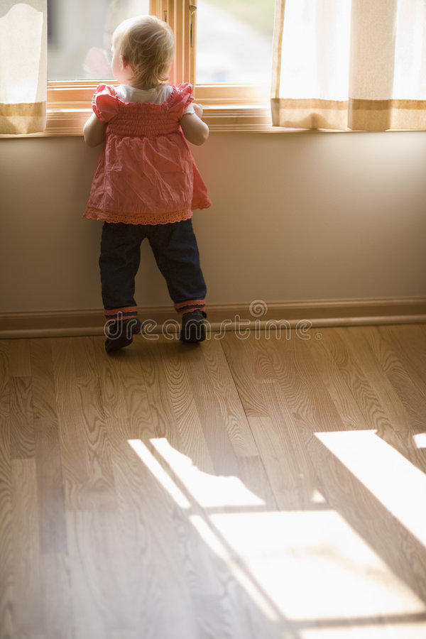младенец смотря вне окно стоковые изображения