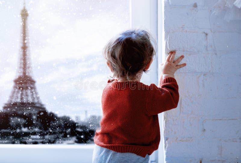 Младенец смотря на Эйфелевой башне во времени снега стоковое фото rf