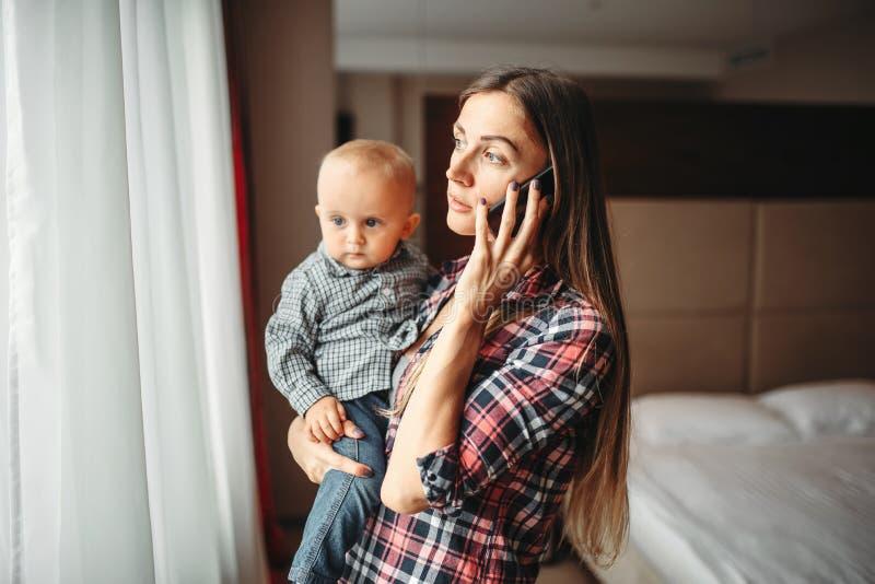 Младенец удерживания матери в оружиях и говорить по телефону стоковая фотография rf
