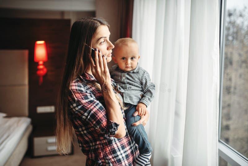 Младенец удерживания матери в оружиях и говорить по телефону стоковое фото rf
