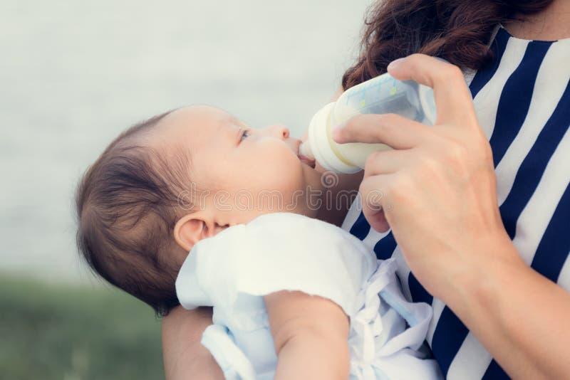 Младенческий младенец на быть поданным ее питьевым молоком матери от бутылки стоковые изображения rf