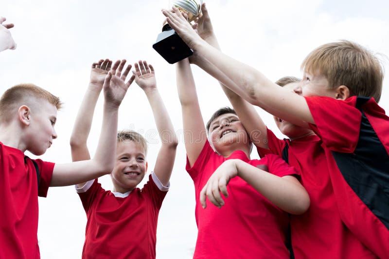 Младшая команда держа чашку трофея стоковое фото rf
