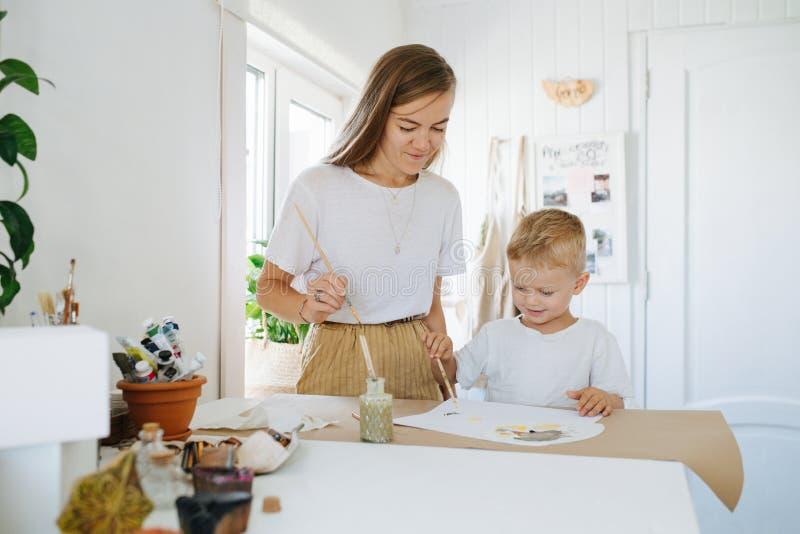 Младшая мать и сын первого класса рисуют вместе дома стоковое изображение