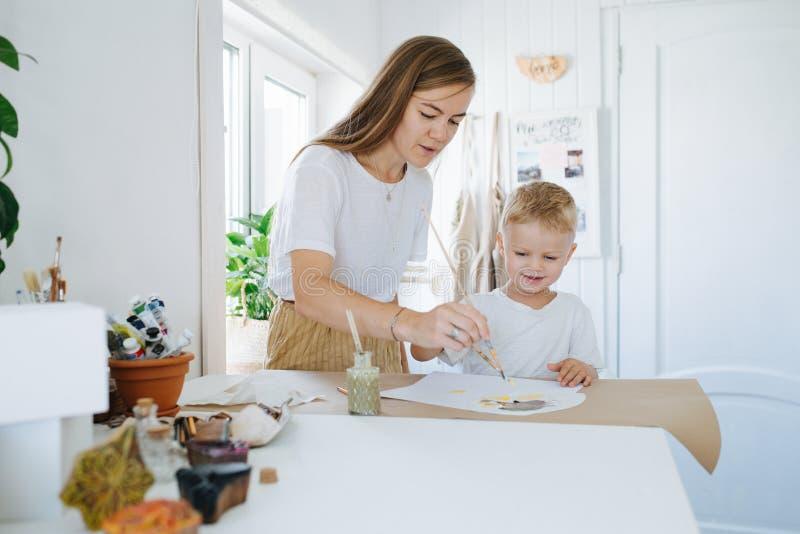 Младшая мать и сын первого класса рисуют вместе дома стоковые изображения rf