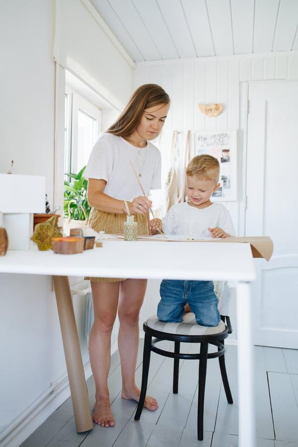 Младшая мать и сын первого класса рисуют вместе дома стоковая фотография