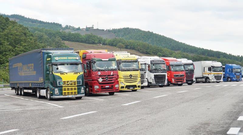 Многие грузовики стоят на стоянке возле шоссе стоковые изображения rf