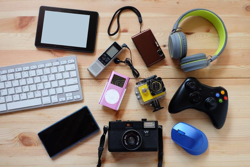 Многие использовали современные электронные устройства для повседневного использования на деревянном полу, концепции повторного и стоковое фото