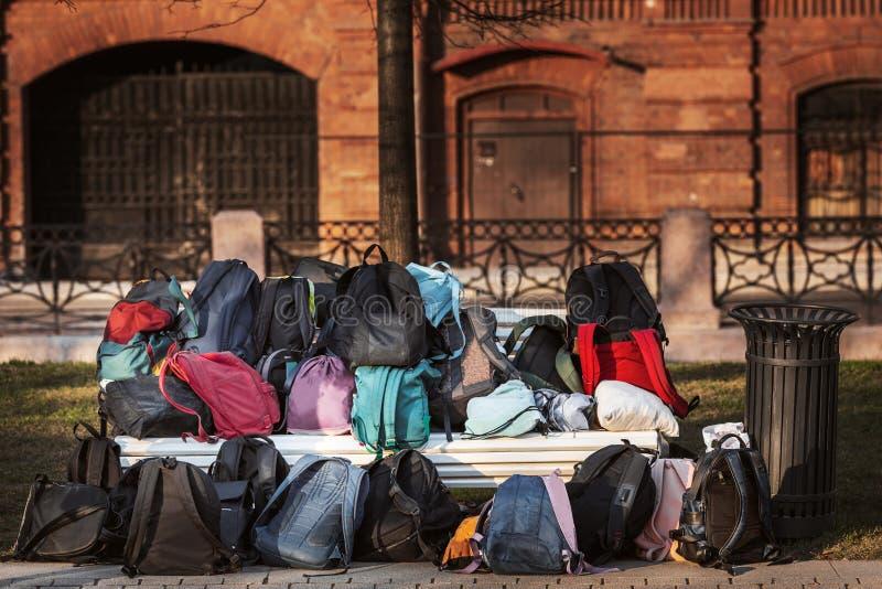 Многие школьные рюкзаки На траве и скамье лежит куча рюкзаков и сумок некоторые вещи остались в солнечном общественном парке стоковая фотография
