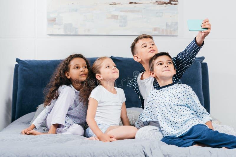 многокультурная группа в составе дети принимая selfie на смартфоне стоковые изображения
