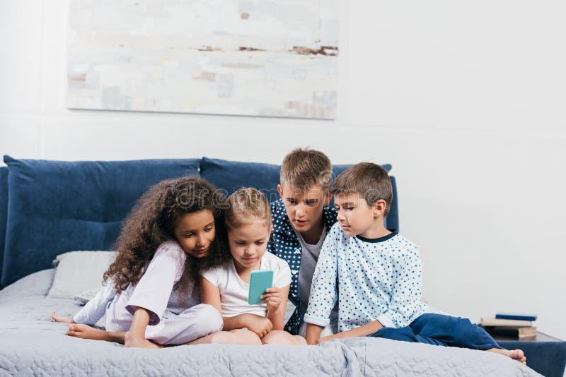 многокультурные дети сидя на кровати совместно и используя смартфон стоковые изображения rf