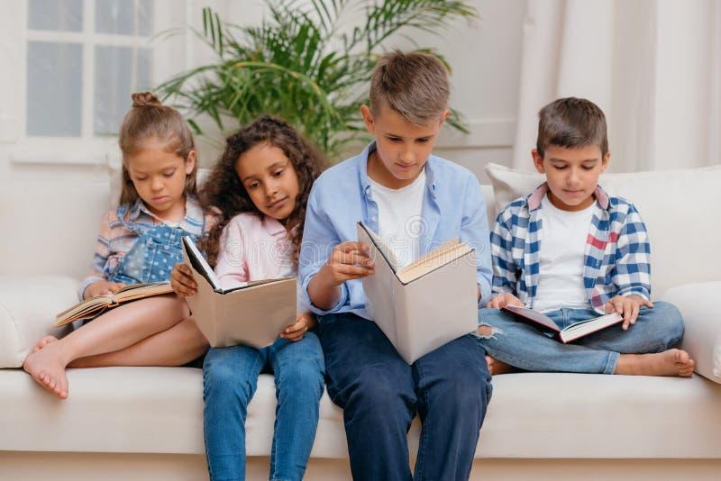 Многокультурная группа в составе сфокусированные книги чтения детей пока сидящ на софе стоковые изображения