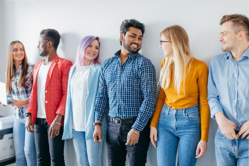 Многонациональная группа в составе молодые люди в вскользь носке изолированное над серой предпосылкой стоковое изображение