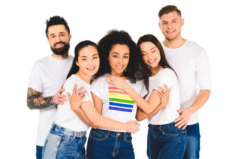 многонациональная группа в составе молодые люди усмехаясь и обнимая с Афро-американской женщиной со знаком lgbt на изолированной  стоковое изображение