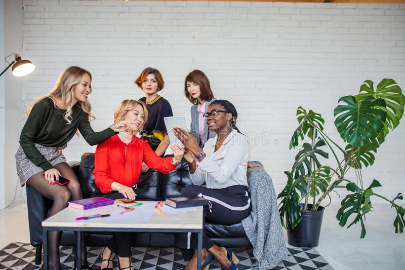 Многонациональная женская команда аплодируя во время семинара дела в конференц-зале стоковые изображения rf