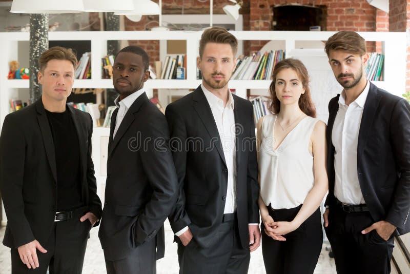 Многонациональная команда представляя уверенно в офисе стоковая фотография rf