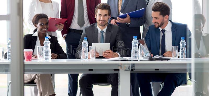 Многонациональная команда работников на таблице стоковое фото