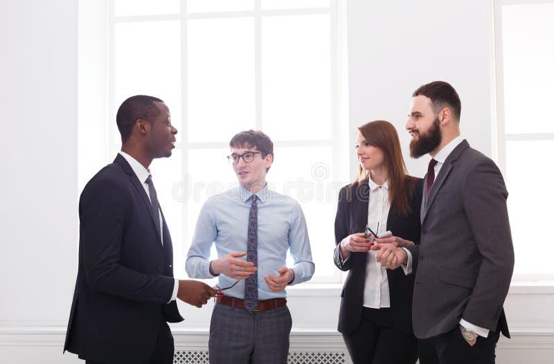 Многонациональная корпоративная встреча успешных менеджеров в офисе, бизнесменов с космосом экземпляра белизна офиса жизни фоново стоковые изображения