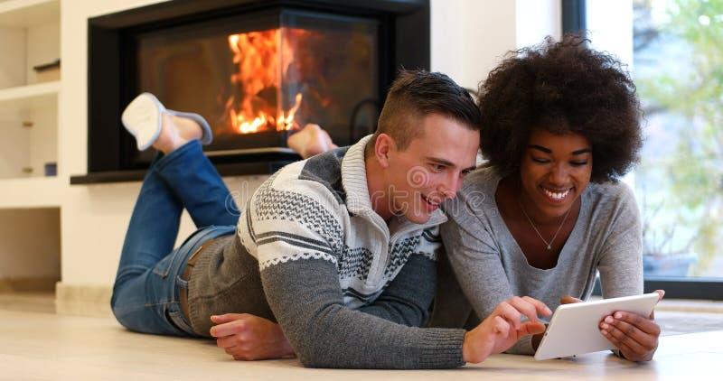 Многонациональные пары используя планшет на поле стоковая фотография