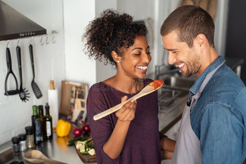 Многонациональные пары пробуя еду от деревянной ложки стоковое изображение rf