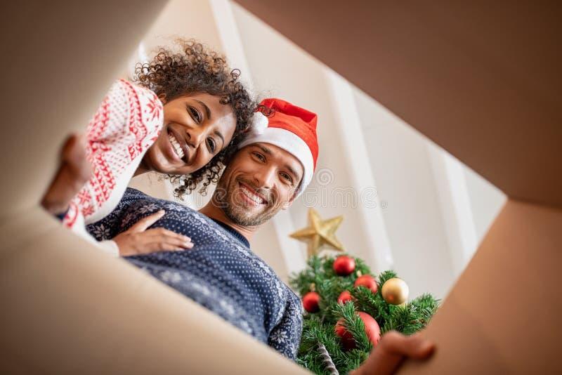 Многонациональные пары распаковывая подарок на рождество стоковое изображение