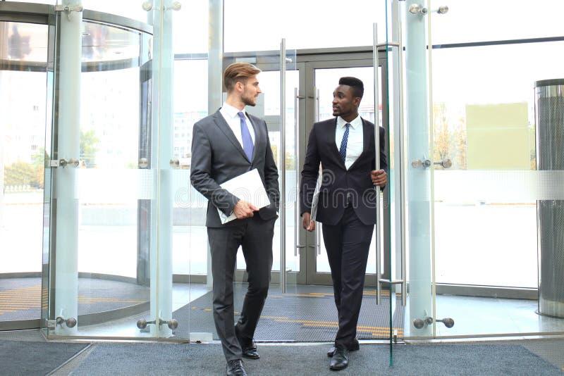 2 многонациональных молодых бизнесмена входя в в офисное здание с стеклянными дверями стоковые изображения