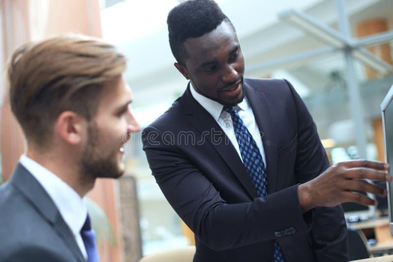 2 многонациональных молодых бизнесмена, смотря ПК пока обсуждающ проект работы сидя на столе в современном офисе стоковые изображения