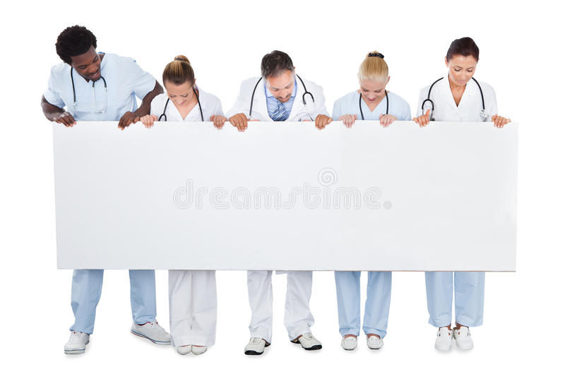 Многонациональная медицинская бригада смотря пустую афишу стоковое фото