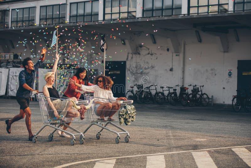 Многонациональное молодые люди участвуя в гонке с вагонетками покупок стоковая фотография