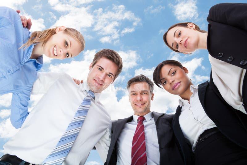 Многонациональные бизнесмены формируя груду против неба стоковые изображения rf