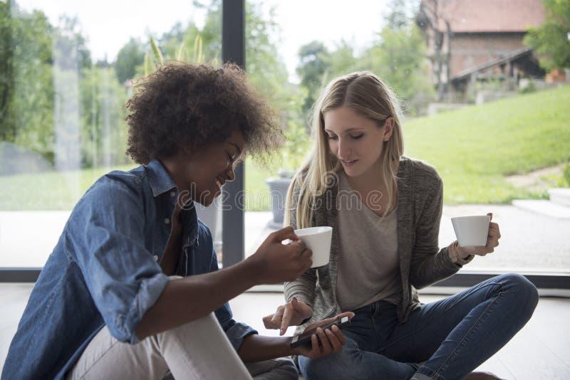 Многонациональные женщины сидят на поле и выпивая кофе стоковые фото