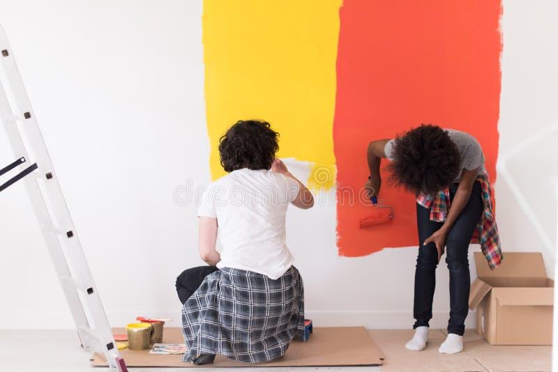 Многонациональные пары крася внутреннюю стену стоковое фото rf