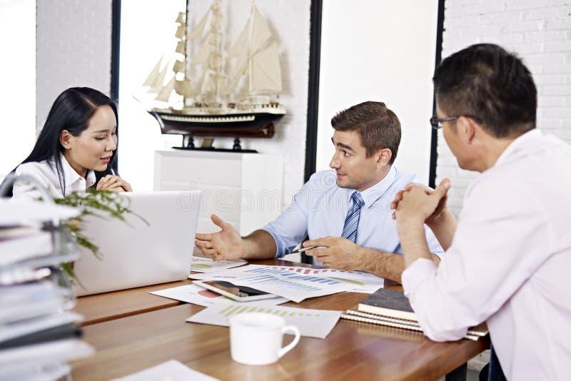 Многонациональные предприниматели обсуждая представление продаж внутри  стоковые изображения rf
