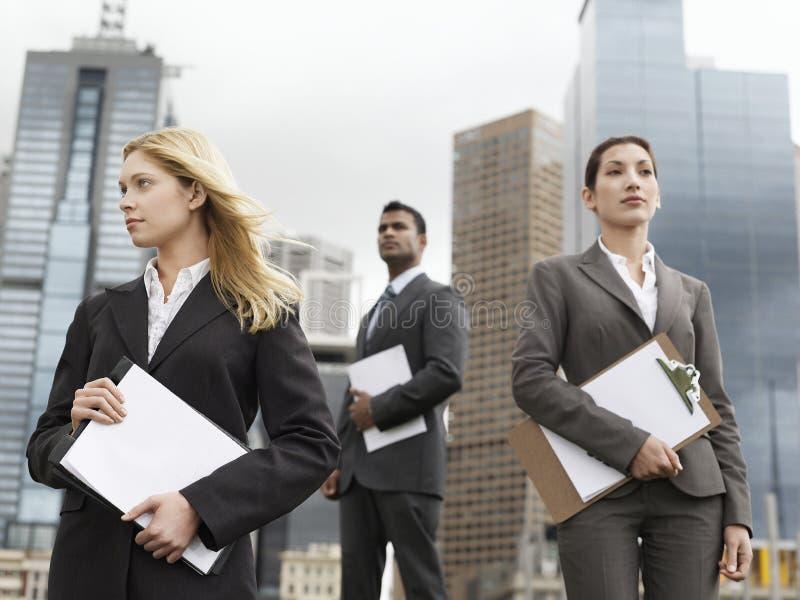Многонациональные предприниматели с досками сзажимом для бумаги против зданий стоковая фотография