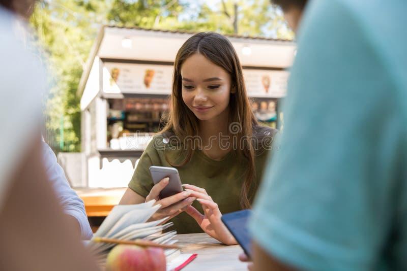 Многонациональные студенты друзей используя мобильные телефоны стоковая фотография rf