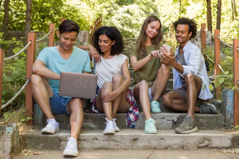 Многонациональные студенты друзей outdoors используя мобильный телефон и компьтер-книжку стоковые фото