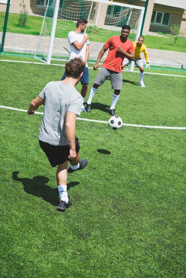 Многонациональные футболисты во время футбольного матча на тангаже стоковое изображение rf