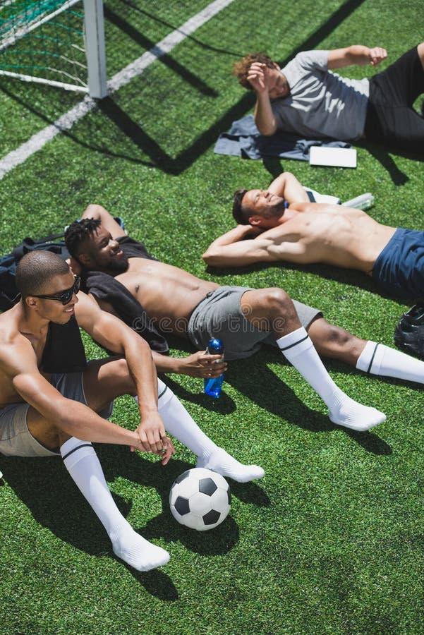 Многонациональные футболисты отдыхая на футбольном поле после игры стоковые фото